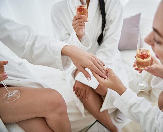 Beautiful jewelry. Ladies in white bathrobes holding glasses of champagne and looking at arm of future bride. Women sitting on daybeds at spa salon