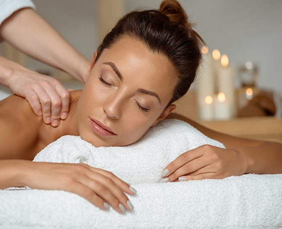 Young attractive brunette girl having massage relaxing in spa salon. Eyes closed. Copy space.